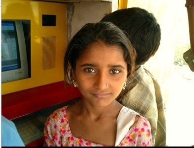An Indian student in front of a Hole in the Wall education kiosk.