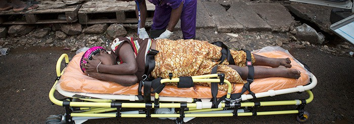 A pregnant woman lays by herself on a stretcher as people watch from a distance, afraid to touch her as she is suspected of having Ebola, in Freetown, Sierra Leone.
