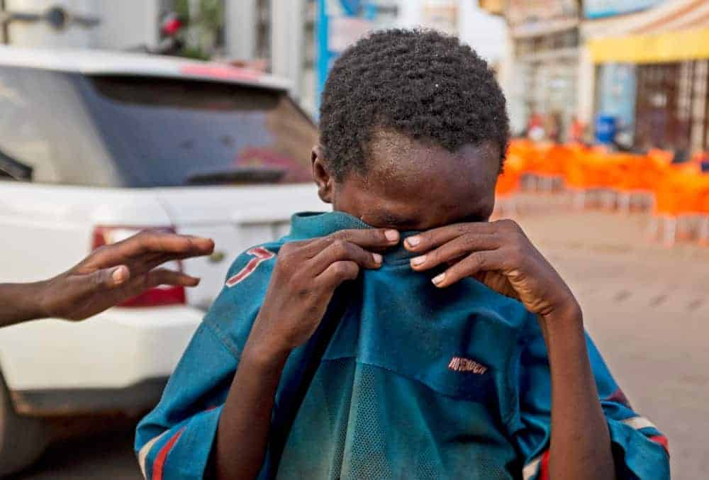 A street child crying consoled by his friend in Ouagadougou Burkina Faso