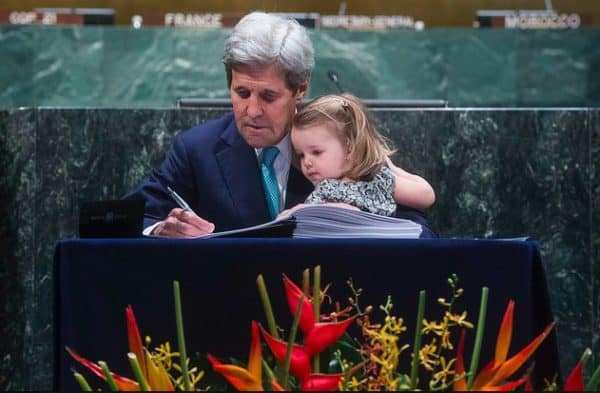 John Kerry, US secretary of state, signing the Paris Agreement on climate change in the UN General Assembly, April 22, 2016, with a granddaughter. AMANDA VOISARD/UN PHOTO
